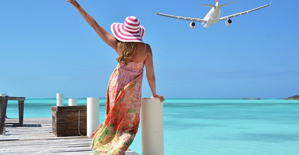 A woman on a pier waves goodbye to a departing plane.