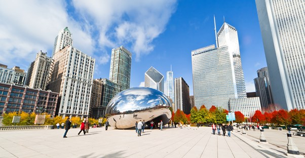 millennium park and the cloud gate sculpture against a backdrop of the chicago skyline