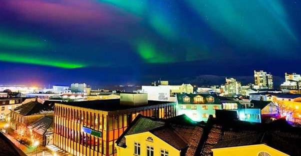 The Norther Lights (Aurora Borealis) over quaint buildings