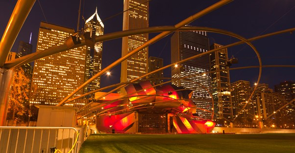 jay pritzker pavilion at night bathed in red light against a backdrop of the chicago skyline