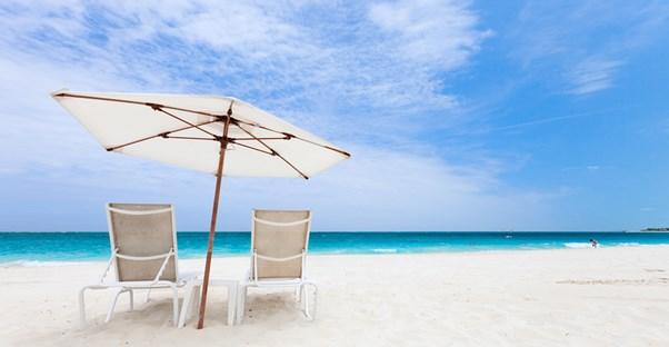 two empty beach chairs undearneath an umbrella on the beach