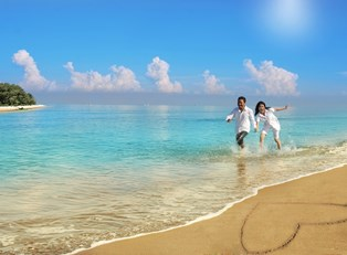 a couple holding hands running along the ocean with a heart drawn in the beach sand