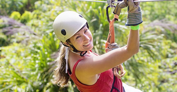 a woman about to ride a zipline through a Caribbean tropical jungle