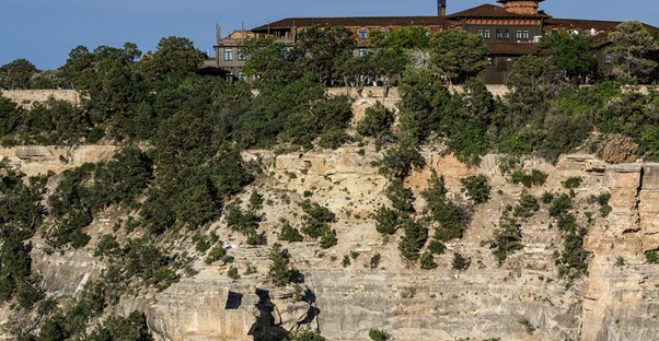 a large wooden hotel sits on the edge of the North Rim of the Grand Canyon