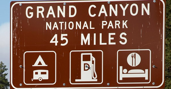 a brown road sign stating that the Grand Canyon is 45 miles away
