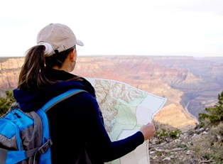 a female hiker examines her map while standing on the edge of the Grand Canyon