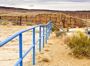 a railed lookout point at the edge of the southern rim of the grand canyon