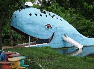 a blue whale-shaped bridge across a pond along route 66