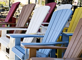 colorful adirondack chairs sit facing the Gulf of Mexico in Sanibel Island, Florida