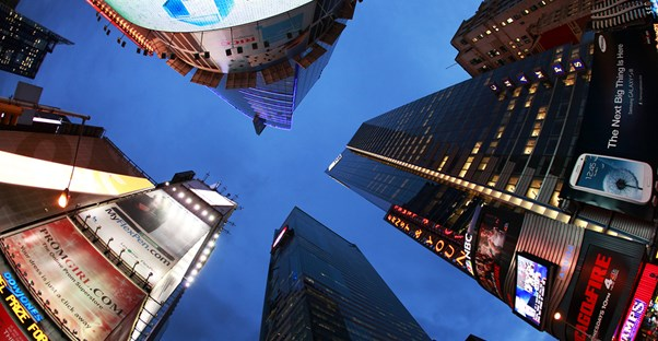 a view upwards towards the sky through the buildings from the center of Times Square