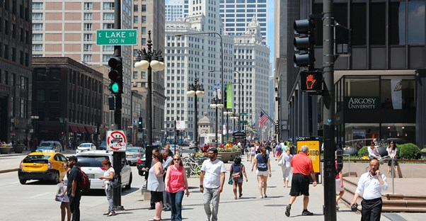 people bustle down Chicago's Magnificent Mile on Michigan Avenue