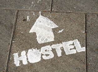 the word hostel is spraypainted on the ground with an arrow pointing the way