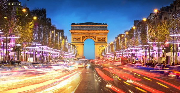 the arc de triomphe is light up colorfully at night