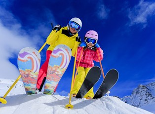 a mom and daughter get set to ski down a mountain slope