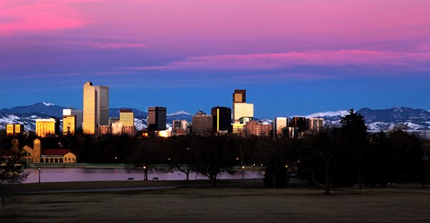 the skyline of Denver in front of a pink sunset sky