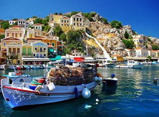 a boat sits in the colorful harbor of a greek island community
