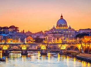 St. Peter's Basilica is lit up by colorful lights at night