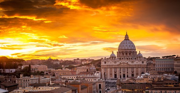 the sun rises behind st. peter's basilica