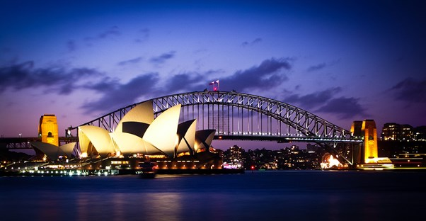 the sydney opera house is lit up at night in front of the sydney harbour bridge