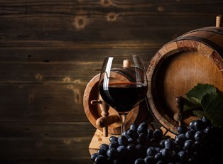 a glass of wine sits in front of a wine barrel and sonoma california grapes