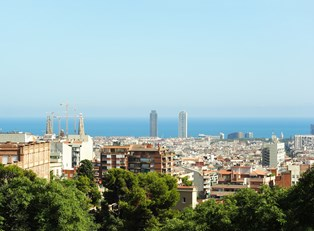 the barcelona skyline extends to the ocean on a sunny day