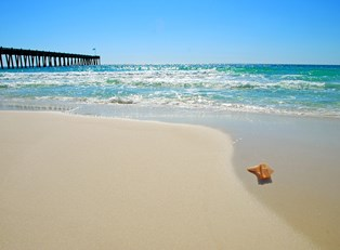a pier extends beyond the Gulf Shores beach into the Gulf of Mexico