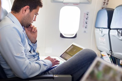 A typical business traveler checks his laptop for updates while on a plane.