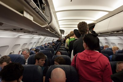 Passengers crowd an airplane aisle trying to pack away their luggage.