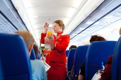 A flight attendant shows the proper way to put on an oxygen mask.