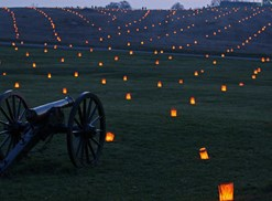 Antietam Battlefield lit up with orange luminaries at nighttime.