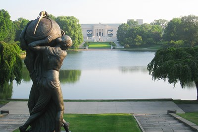 A sculpture with its back to the camera overlooks the reflecting pool in front of the Cleveland Museum of Art.