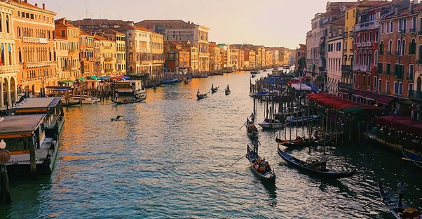Boats float down a Venetian canal.