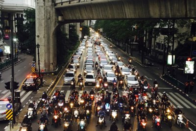 A long stretch of cars and motorcycles stop at a stoplight in Bangkok, Thailand.