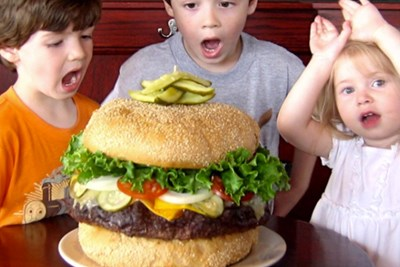 Surprised kids stand around the Absolutely Ridiculous Burger at Mallies Sports Grill and Bar in Michigan.
