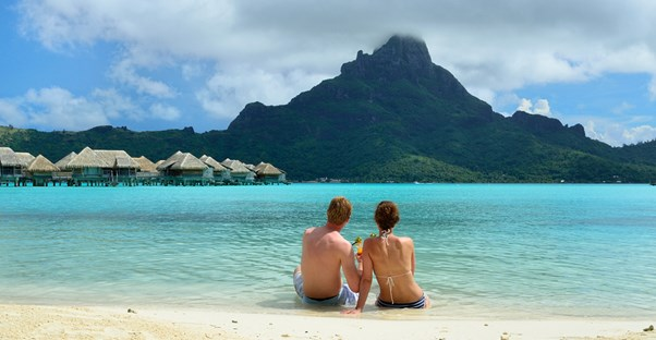 a honeymooning couple sits on the beach overlooking the ocean and resort bungalows
