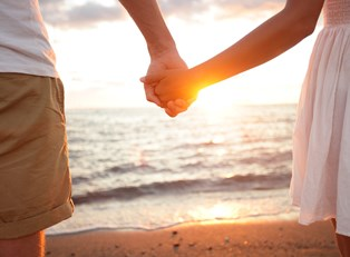 a honeymooning couple holding hands on the beach in front of the sunset