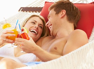 a honeymooning couple cheers cocktails in a hammock