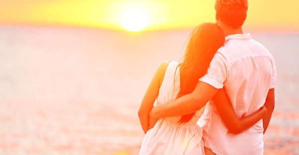 a honeymooning couple embraces in front of an ocean sunset