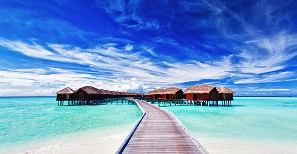 a boardwalk leading to bora bora resort huts located on stilts over the ocean waters