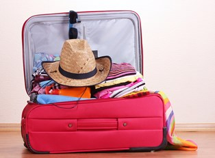 a suitcase overflows with closes and a cowboy hat