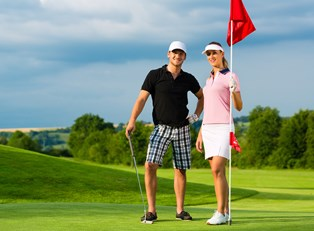 a couple stands triumphant at the final hole of a challenging golf course