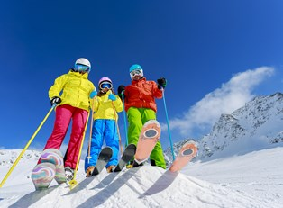 a family of skiers stands at the top of a run about to ski down