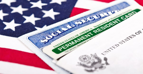 Social Security Card and Permanent Resident Card laying on an American flag