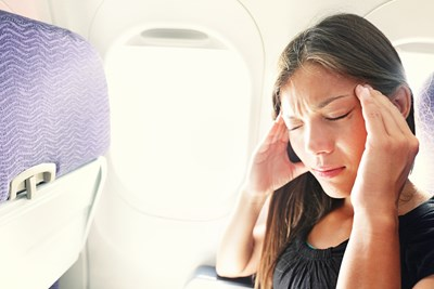 A woman massages her head while suffering from jet lag on her flight.