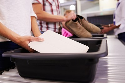 Airline passengers place their electronics and shoes into screen bins at a TSA checkpoint.