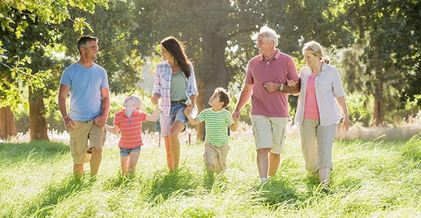 A family of children, parents, and grandparents holds hands while walking through a field.