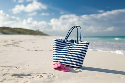 A beach bag and flipflops on a beach.