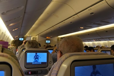 A man watches a movie on a plane during his long flight.