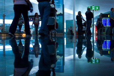 Passengers walk through a busy airport concourse toward airport security.