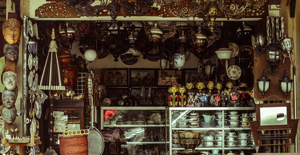 A shop stall at an open-air market displays multiple wares and knickknack.
